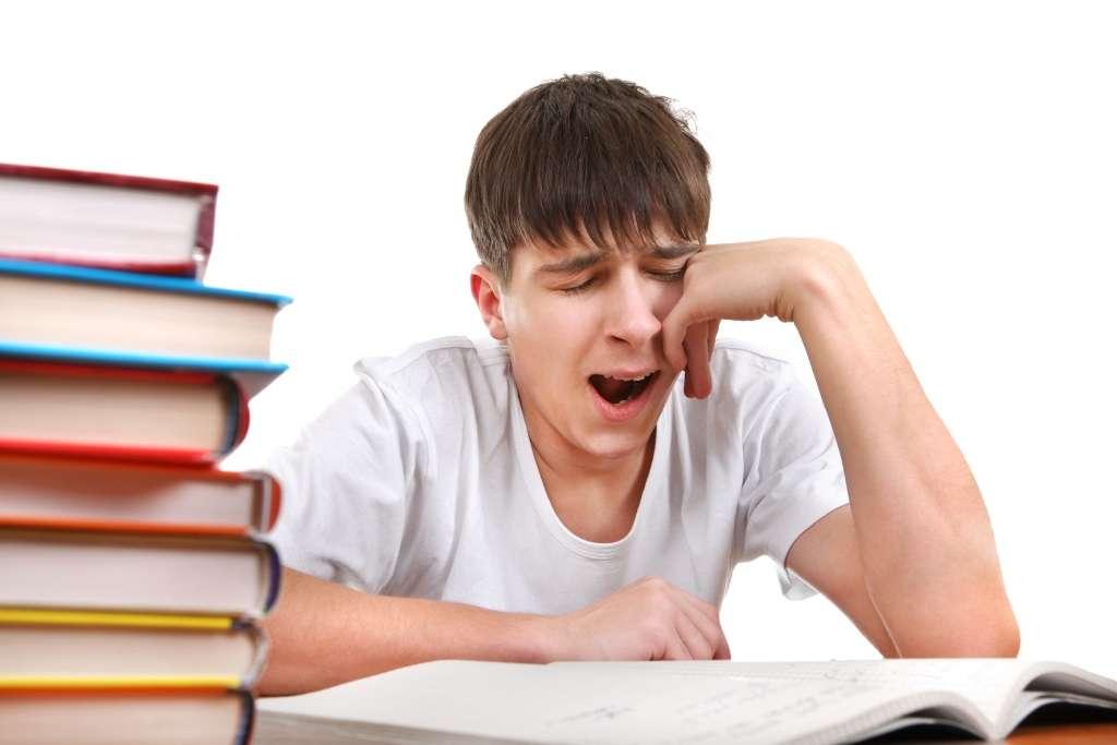 Aluno cansado e com sono durante estudos: menos horas de descanso e de sono geram mal desempenho escolar